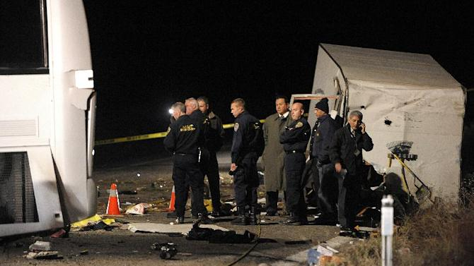 Authorities continue their investigation of the scene where at least eight people were killed and 38 people were injured after a tour bus, left, carrying a group from Tijuana, Mexico crashed with two other vehicles just north of Yucaipa, Calif., Sunday, Feb. 3, 2013. (AP Photos/Rodrigo Pena)