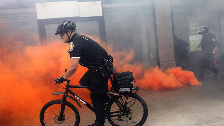 A Seattle police officer rides past a smoke bomb after protesters shattered windows in downtown businesses during a May Day rally on Tuesday, May 1, 2012 in downtown Seattle. Mayor Mike McGinn says he's making an emergency declaration allowing police to confiscate items that can be used as weapons following violent May Day protests that left storefronts and car windows shattered. (AP Photo/Seattlepi.com, Joshua Trujillo)