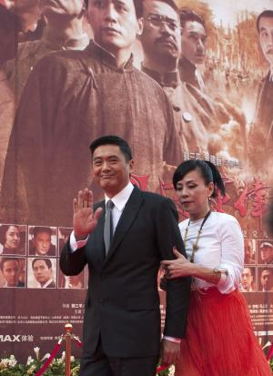 "Hong Kong actor Chow Yun-fat, left, accompanied by his wife, waves at fans during the movie premiere for ""Beginning of the Great Revival"" in Beijing, China, Wednesday, June 8, 2011. Chinese movie stars have gathered to launch the blockbuster propaganda movie celebrating the 90th anniversary of the Chinese Communist Party. (AP Photo/Andy Wong)"