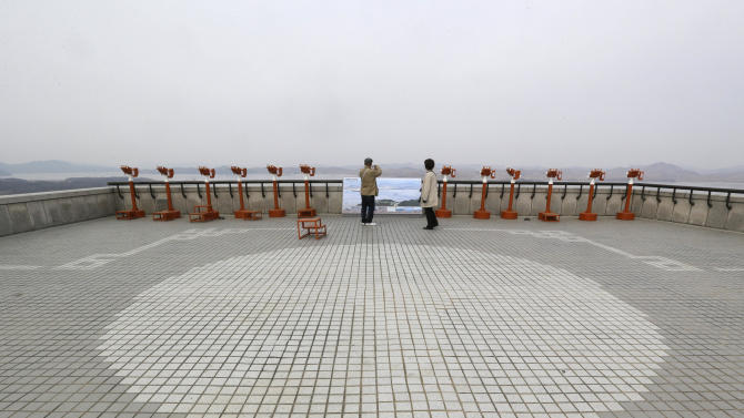 """Visitors take pictures North Korean territory at the unification observation post near the border village of Panmunjom, that has separated the two Koreas since the Korean War, in Paju, north of Seoul, South Korea, Saturday, March 30, 2013. North Korea issued its latest belligerent threat Saturday, saying it has entered """"a state of war"""" with South Korea a day after its young leader threatened the United States because two American B-2 bombers flew a training mission in South Korea. (AP Photo/Lee Jin-man)"""