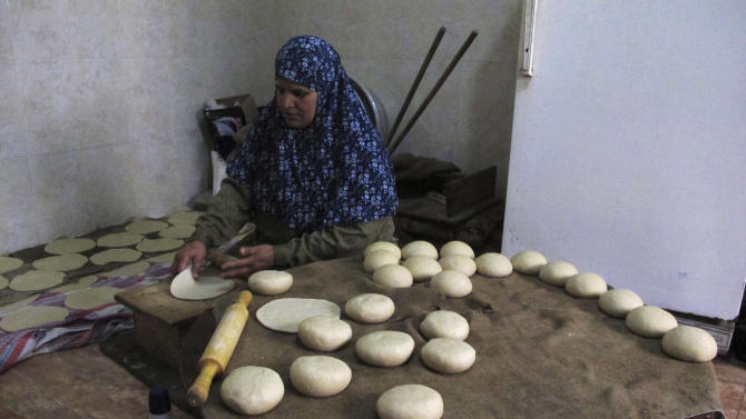 """In this Monday, March 18, 2013 photograph, Palestinian Nabila Qishta, 52, prepares bread in the southern Gaza Strip town of Rafah, using flour donated by the U.N. Gaza cuisine is Mediterranean-based, relying on olive oil, fresh vegetables, herbs and grains. """"The Gaza Kitchen"""" is being praised by celebrity chefs like Anthony Bourdain for showcasing a unique, fiery variation of Mediterranean cuisine kept alive through blockade, war and impoverishment. (AP Photo/Diaa Hadid)"""