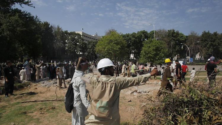 Pakistani protesters use slingshot to shoot a stone towards police during a clash near the house of Prime Minister Nawaz Sharif in Islamabad, Pakistan Sunday, Aug. 31, 2014. Pakistani police clashed with scattered pockets of anti-government protesters trying to advance on the prime minister's residence after a night of violence that saw hundreds wounded and the first death in more than two weeks of demonstrations. (AP Photo/Anjum Naveed)