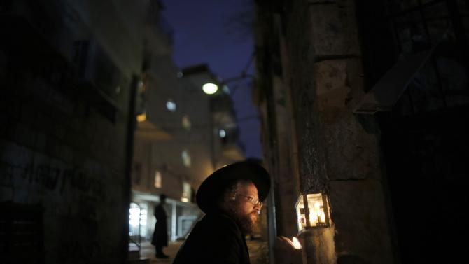 An Ultra-Orthodox Jewish man lights a candle on the sixth night of the holiday of Hanukkah in Jerusalem