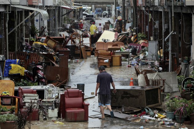 A man walks down a lane of water damaged furniture from heavy rains brought by Typhoon Tembin in Pingtung county, Taiwan, Friday, Aug. 24, 2012.