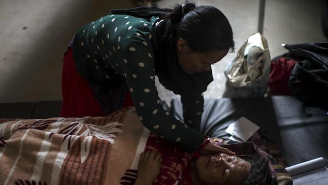 Woman comforts another woman who is being treated at Gorkha hospital following Saturday's earthquake, in Gorkha
