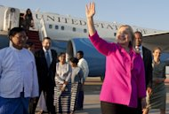US Secretary of State Hillary Rodham Clinton waves alongside Myanmar Deputy Foreign Minister Myo Myint, left, upon her arrival by her airplane in Naypyidaw, Myanmar, Wednesday, Nov. 30, 2011. Making a diplomatically risky trip to the long-isolated Southeast Asian nation of Myanmar, Clinton said she wanted to see for herself whether new civilian leaders are truly ready to throw off 50 years of military dictatorship _ a test that includes rare face-to-face meetings with former members of the junta whose brutal rule made a poor pariah state of one of the region's most resource-rich nations. (AP Photo/Saul Loeb, Pool)