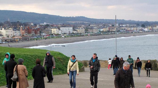 This Feb. 17, 2013 photo shows hikers on the Bray-to-Greystones cliff walk south of Dublin, Ireland. The Victorian resort town of Bray is in the background. The 8-kilometer (5-mile) path offers panoramic views of the Irish Sea and is among the most popular in the greater Dublin area. (AP Photo/Shawn Pogatchnik)