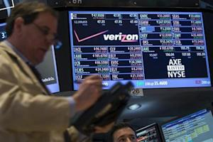A trader works by the post where Verizon is traded on the floor of the New York Stock Exchange