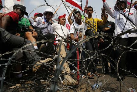 Supporters of presidential candidate Prabowo Subianto stomp on a barricade during a protest near the Constitutional Court in Jakarta
