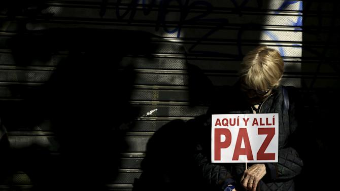 """A woman holds a placard reading """"Here and there Peace"""" during a protest against militant attacks and war, in Madrid"""
