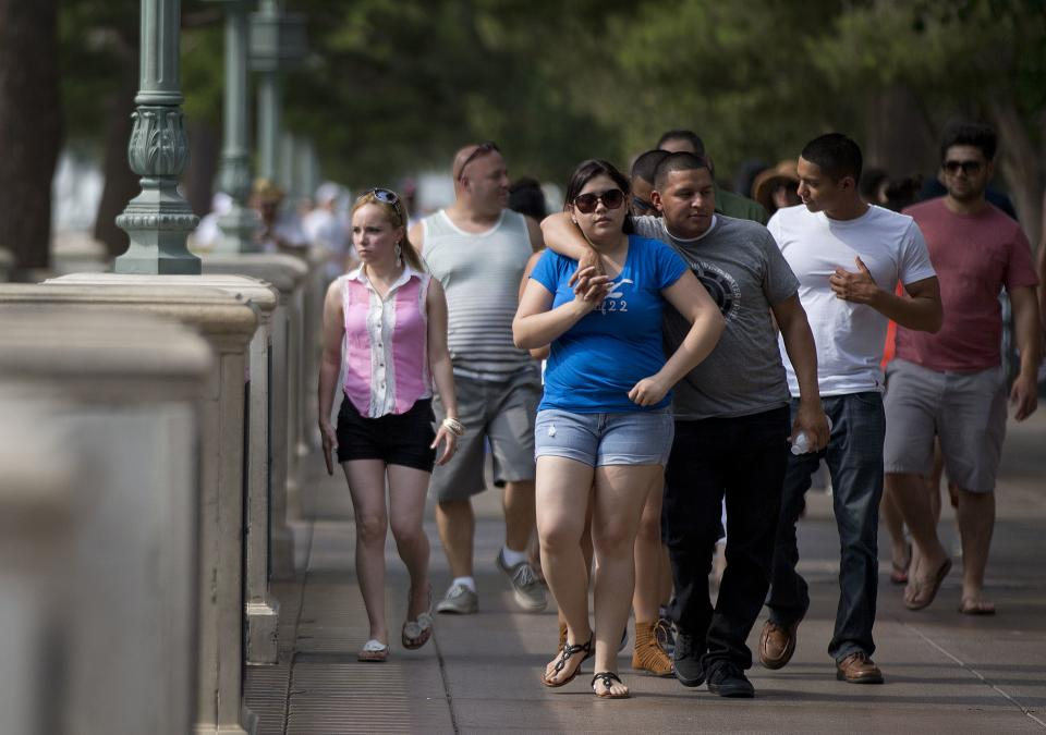 Tourists walk in the shade of trees along The Strip in Las Vegas on Saturday, June 29, 2013. Saturday's daytime high was expected to reach 117 degrees, which is the city's all-time high. It was 108 at noon Saturday in Sin City. (AP Photo/Julie Jacobson)