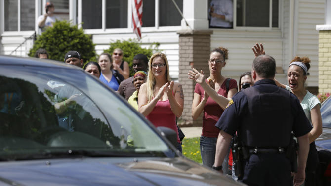 FILE - In this Wednesday, May 8, 2013 file photo, neighbors and friends of Amanda Berry clap as she arrives at her sister's home, in Cleveland. For Gina DeJesus, Berry and Michelle Knight, who were freed from captivity inside a Cleveland house earlier this week, the ordeal is not over. Next comes recovery _ from sexual abuse and their sudden, jarring reentry into a world much different than the one they were snatched from a decade ago. (AP Photo/Tony Dejak, File)