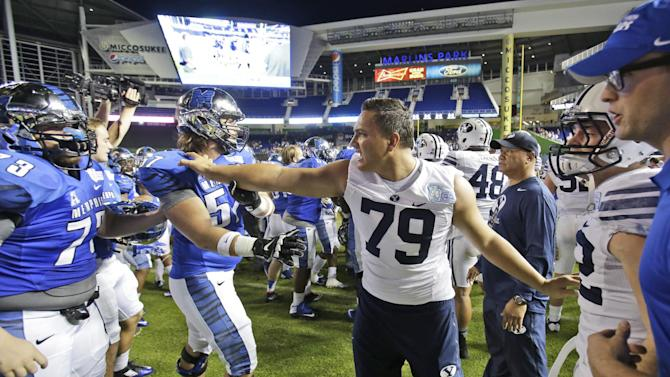 BYU's Latanoa Pikula (79) intercedes in a brawl after Memphis defeated BYU Young 55-48 in two overtimes in the inaugural Miami Beach Bowl NCAA college football game, Monday, Dec. 22, 2014, in Miami. (AP Photo/Wilfredo Lee)