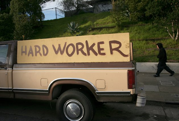 "handmade sign painted on the side of a pickup truck reading ""hard worker"" is shown in San Francisco"