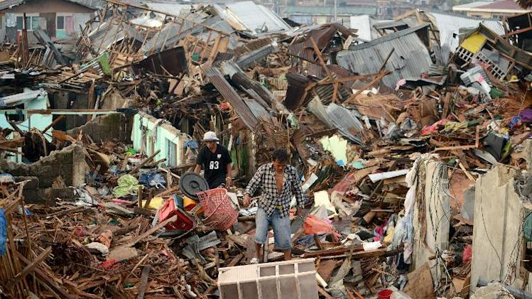 Men search for salvageable materials among destroyed houses in Tacloban, Leyte province, on November 26, 2013