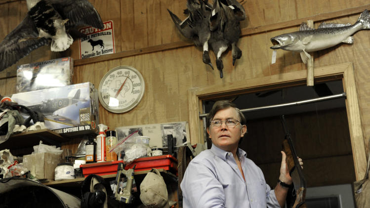In this photo taken Wednesday, Dec. 19, 2012 taxidermist Bill Moos displays one of his shotguns in his shop in Bryan, Texas. Moos, who owns a collection of more than 30 guns, can be spotted any given morning, prowling his roughly 40-acre (16-hectare) ranch with his dogs and a shotgun slung over his shoulder. (AP Photo/Pat Sullivan)