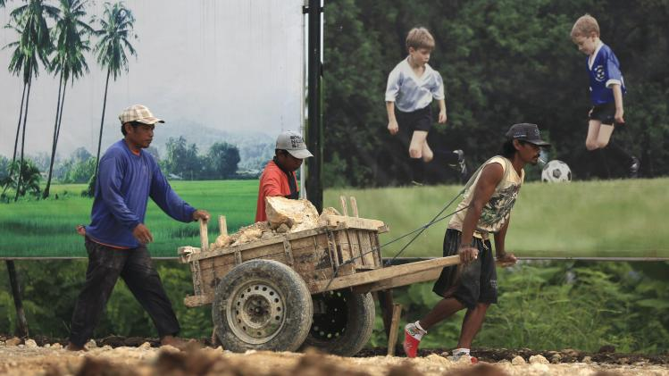Workers transport rocks with the aid of a wooden cart at a construction housing complex in Tangerang,