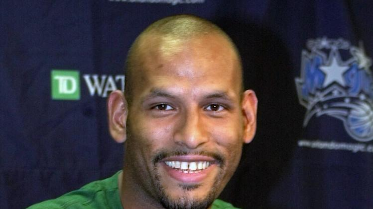 "FILE- John Amaechi, the first British player to start in an NBA game, playfully covers a tee shirt that states ""Amaechi Tea Co."" at a news conference in Orlando, Fla. USA, in this file photo dated Tuesday Aug. 8, 2000.  Amaechi became the first openly gay former NBA player with a landmark public statement in 2007, three years after retiring, but in a telephone interview with The Associated Press, Amaechi disclosed that he is in contact with gay English Premier League players to advise them about gay issues. (AP Photo/Peter Cosgrove, File)"