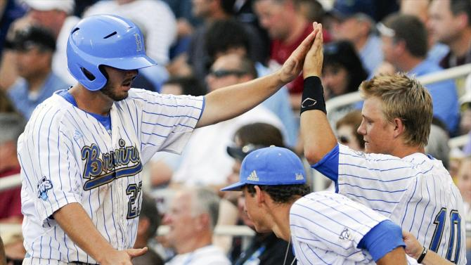 UCLA's Pat Gallagher, left, is greeted by teammates including Pat Valaika (10) after scoring against North Carolina on a single by Cody Regis in the second inning of an NCAA College World Series baseball game in Omaha, Neb., Friday, June 21, 2013. (AP Photo/Eric Francis)