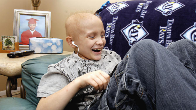 In this photo taken Jan. 19, 2011, nine-year-old Dylan Hanlon laughs while playing a game on a portable computer at home in Holiday, Fla.  Dylan is currently undergoing chemotherapy for Ewing's sarcoma. (AP Photo/Chris O'Meara)