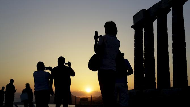Tourists take photographs at the Temple of Poseidon in Cape Sounion in Greece