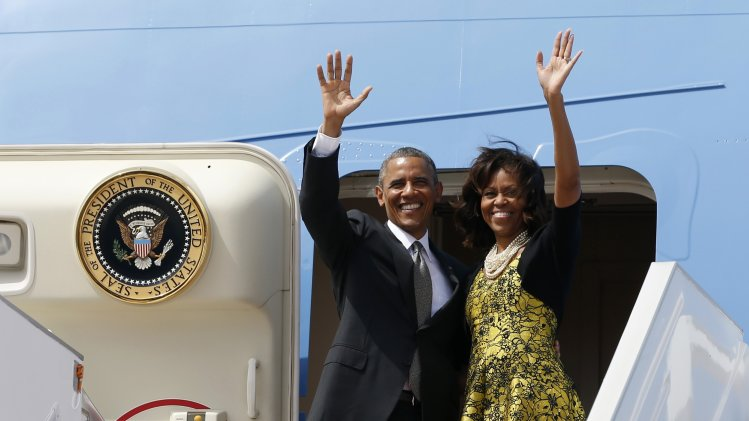 U.S. President Barack Obama and first lady Michelle Obama wave from Air Force One as they depart Dakar