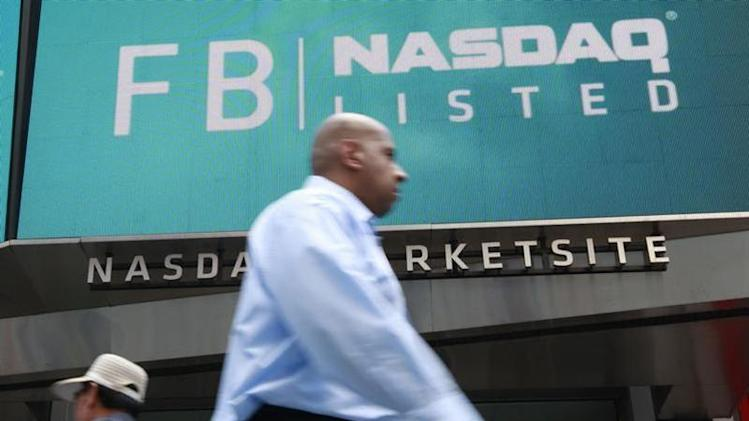 Man walks past sign welcoming Facebook to NASDAQ Marketsite in New York