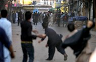 pakistani Shiite and Sunni Muslims throw stones at each other during a clash at an Ashura procession in Rawalpindi on November 15, 2013