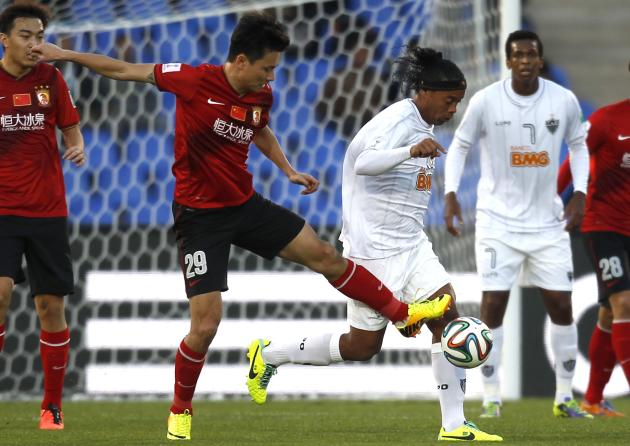 Ronaldinho of Brazil's Atletico Mineiro fights for the ball with Gao Lin of China's Guangzhou Evergrande during their 2013 FIFA Club World Cup third place soccer match in Marrakech stadium