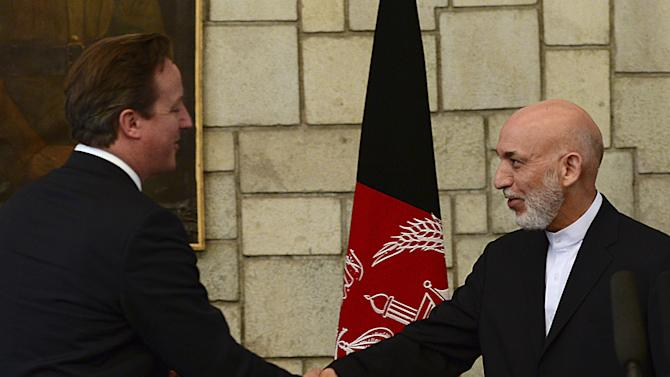 Afghan President Hamid Karzai, right, shakes hands with British Prime Minister David Cameron during a press conference at the presidential palace in Kabul, Afghanistan, Saturday, June 29, 2013. Karzai urged Taliban militants to sit down at the negotiating table, saying Saturday his government is still willing to start peace talks with the insurgents despite an attack by the group on the presidential palace this week. (AP Photo/Massoud Hossaini, Pool)