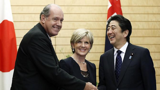 Australia's Defense Minister David Johnston, left, and Foreign Minister Julie Bishop, center, pose for photos with Japan's Prime Minister Shinzo Abe at Abe's official residence in Tokyo, Wednesday, June 11, 2014. Japan and Australia plan to move ahead with plans to develop a highly stealth submarine technology this week, as Abe pushes to give his country a more assertive global military role. (AP Photo/Yuya Shino, Pool)