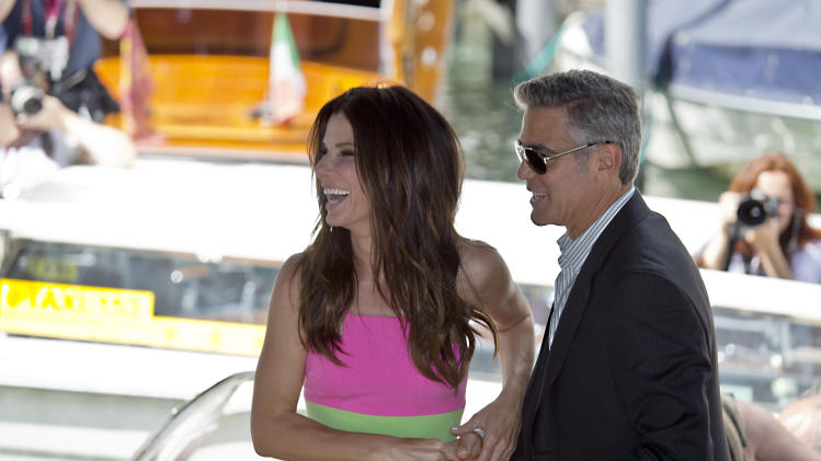 Actors Sandra Bullock and George Clooney arrive to promote their film Gravity at the 70th edition of the Venice Film Festival held from Aug. 28 through Sept. 7, in Venice, Italy, Wednesday, Aug. 28, 2013. (AP Photo/David Azia)
