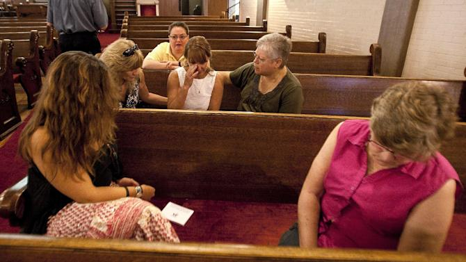 Judy Goos shares her first hand experience of arriving at the scene and helping kids in the shooting as she sits in a pew at the Grant Avenue United Methodist Church in Aurora, Colo. on Sunday, July 22, 2012. She arrived minutes after the shooting since her daughter Emma Goos, 19, was in theater nine and called her right after she called 911. When Goos and her husband arrived on scene they began to help a number of youths they knew through their children. (AP Photo/Barry Gutierrez)