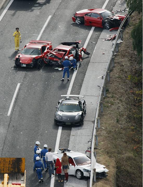 Police officers investigate damaged luxuary cars at the site of a traffic accident on the Chugoku Expressway in Shimonoseki, southwestern Japan, Sunday, Dec. 4, 2011. Thirteen sports cars, including e