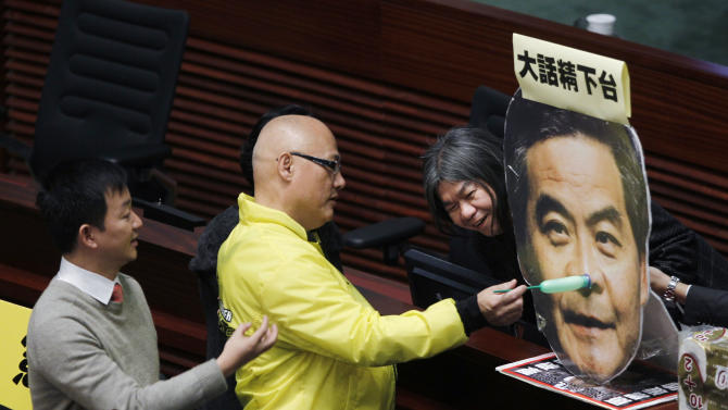 """Hong Kong pro-democracy lawmakers from right, Leung Kwok-hung, Albert Chan and Raymond Wong set up a cutout of the head of Chief Executive Leung Chun-ying with """"Pinocchio's nose"""" and a sign which reads """"Liar steps down"""" before Chief Executive Leung Chun-ying delivering his policy address at the Legislative Council in Hong Kong Wednesday, Jan. 16, 2013. Leung Chun-ying focused on the social problems such as housing, pollution and economic development for the next five years. (AP Photo/Kin Cheung)"""