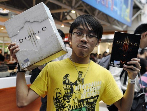 Clerk Seth Chan, 24, poses with his newly released copy of Diablo III and a collector's edition for being the first in line at the videogame's launch event at a computer mall in Singapore on May 15, 2