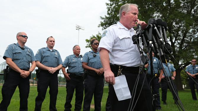 Ferguson Police Chief Tom Jackson is surrounded by his officers as he answers questions at a news conference in Forestwood Park on Friday, Aug. 15, 2014. Jackson took questions in the quiet park after earlier identifying Darren Wilson as the officer who shot Michael Brown. (AP Photo/St. Louis Post-Dispatch, Robert Cohen)