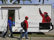 Supporters of Venezuela's late President Hugo Chavez walk past a media trailer as they line up to view his body in state at the Military Academy in Caracas, March 7, 2013. REUTERS/Tomas Bravo