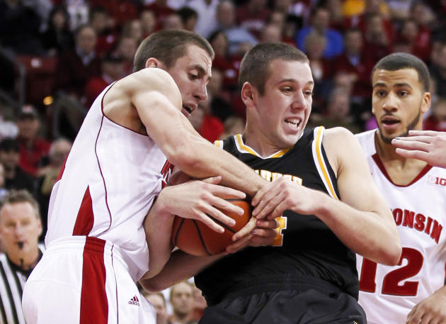 Wisconsin's Josh Gasser, left, and Milwaukee's Austin Arians battle for a rebound during the first half of an NCAA college basketball game on Wednesday, Dec. 11, 2013, in Madison, Wis