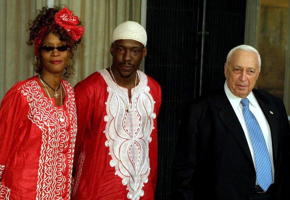 Israeli Prime Minister Ariel Sharon (R) welcomes singer Whitney Houston (L) and her husband/singer, Bobby Brown (C), at the prime minister's residence May 27, 2003 in Jerusalem, Israel. Houston is on 