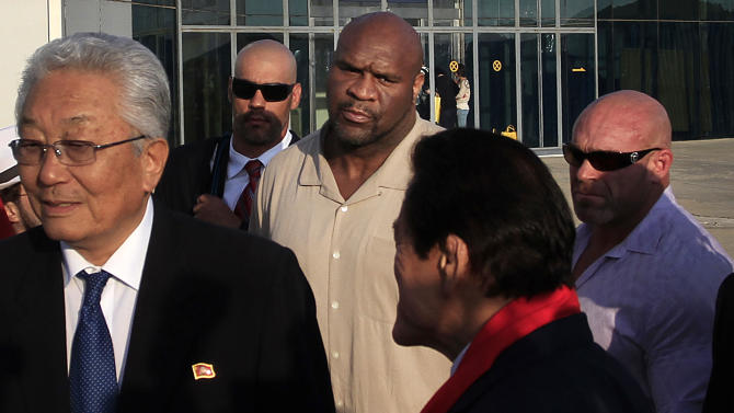 """Former NFL player Bob """"The Beast"""" Sapp, center, arrives at the Sunan International Airport, Thursday, Aug. 28, 2014 in Pyongyang, North Korea. Sapp is participating in a two-day martial arts extravaganza in Pyongyang over the weekend organized by Japanese pro-wrestler turned politician Kanji """"Antonio"""" Inoki in an oddball attempt at sports diplomacy. (AP Photo/Jon Chol Jin)"""