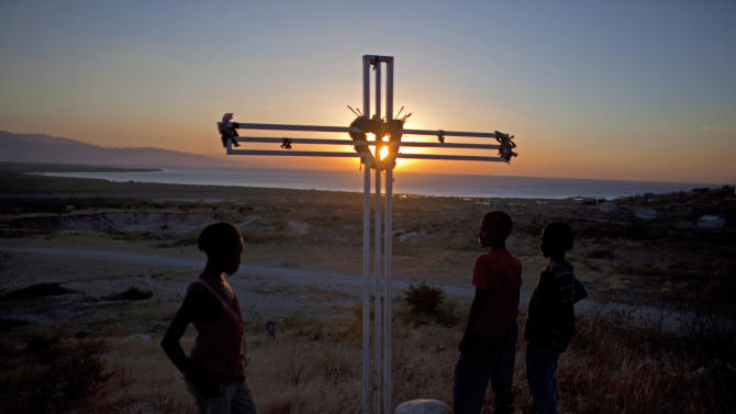 In this picture taken Jan. 8, 2013, a cross memorializing the victims of the 2010 earthquake who are buried at the spot in mass graves is silhouetted against the setting sun in Titanyen, north of Port-au-Prince, Haiti. Saturday marks the third anniversary of the devastating 7.0 magnitude earthquake that destroyed an estimated 100,000 homes across the capital and southern Haiti, including some of the country's most iconic structures. The government put the death toll at 316,000, but no one really knows how many people died. (AP Photo/Dieu Nalio Chery)