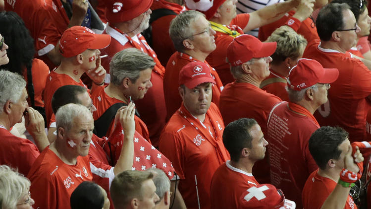 Switzerland fans stand on the tribune during the group E World Cup soccer match between Switzerland and France at the Arena Fonte Nova in Salvador, Brazil, Friday, June 20, 2014. France blew Switzerland away 5-2 to take control of Group E. (AP Photo/Sergei Grits)