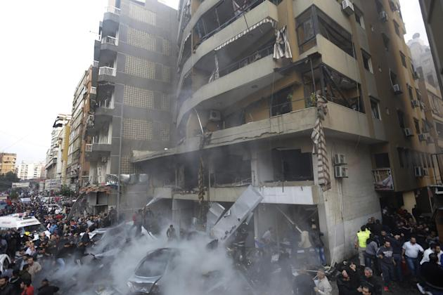 Lebanese citizens gather at the site of an explosion in a stronghold of the Shiite Hezbollah group at the southern suburb of Beirut, Lebanon, Thursday, Jan. 2, 2014. The explosion took place during ru