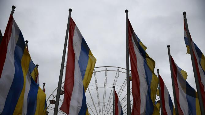 Carnival flags flutters in the wind in front of a partially dismantled ferris wheel during Rosenmontag in Mainz