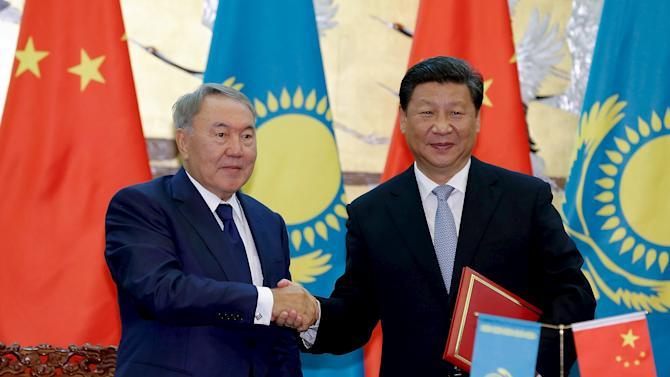 Chinese President Xi Jinping shakes hands with Kazakhstan President Nursultan Nazarbayev during a signing ceremony at the Great Hall of the People in Beijing