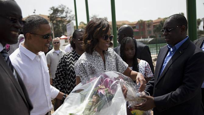 President Barack Obama and first lady Michelle Obama receive flowers after arriving for a tour of Goree Island, Thursday, June 27, 2013, in Goree Island, Senegal. Goree Island is the site of the former slave house and embarkation point built by the Dutch in 1776, from which slaves were brought to the Americas. (AP Photo/Evan Vucci)