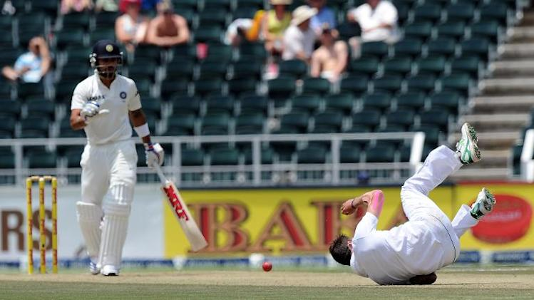 South African bowler Dale Steyn stops a shot from Indian batsman Virat Kohli (left) on the first day of the Test match between South Africa and India at Wanderers Stadium in Johannesburg on December 18, 2013