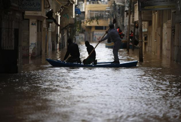 Palestinians travel on a boat on a stormy day in Gaza City