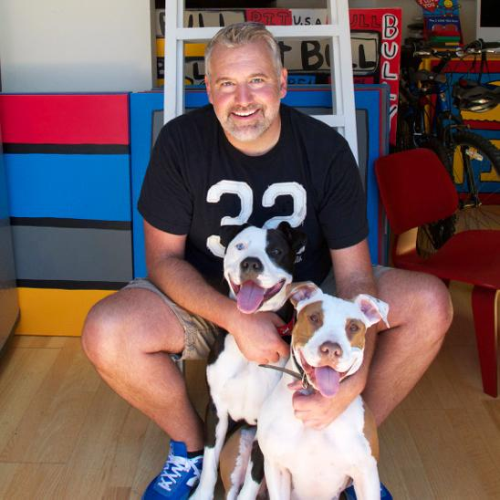 This 2013 photo released by Todd Parr shows children's book author Todd Parr with his dogs Pete, left, and tater Tot in Berkeley, Calif. Parr, 52, relies on playful, brightly-colored drawings and easy-to-understand messages to win over the age 4-to-6 set, along with their teachers and parents. In today's competitive swirl of perfectionism, it's Parr who declares it OK to draw outside the lines, celebrate your big hair and feel lonely sometimes. (AP Photo/Jeff Fielding)